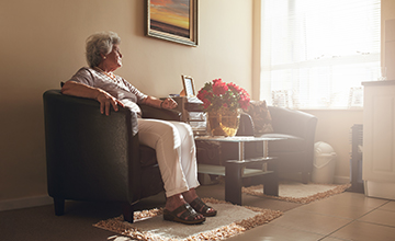 lonely senior woman sitting at home in isolation from COVID-19