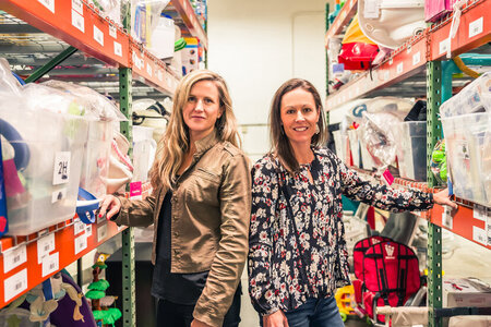 Good Buy Gear co-founders, Kristin Langenfeld and Jessica Crothers smiling in warehouse of used gear