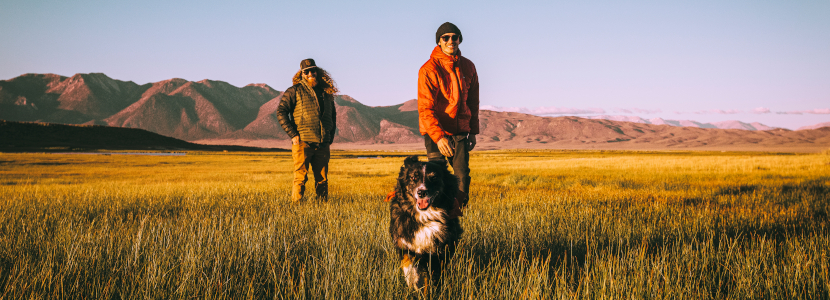 two male hikers watch as their dog runs towards the camera